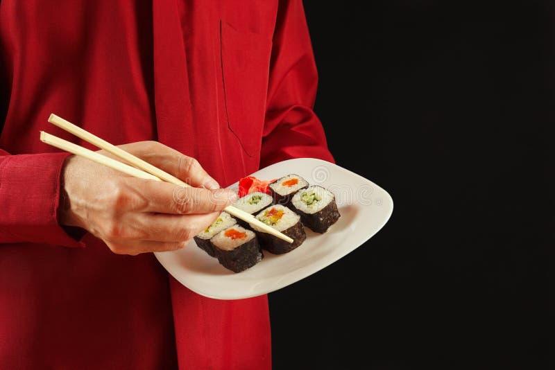 Руки человека в красной рубашке используя палочки принимают крен от плиты на черной предпосылке стоковые фотографии rf