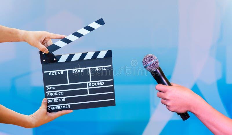 Руки человека держа колотушку кино Концепция режиссера фильма руки держа микрофон в свадебной церемонии интервью или передачи, стоковые изображения