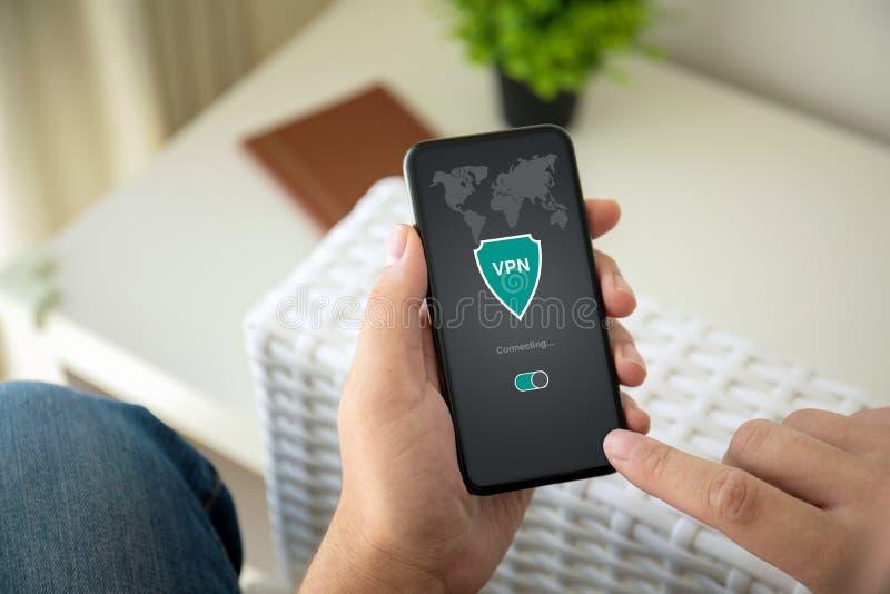 Руки человека держа телефон с частной сетью vpn приложения в комнате стоковые изображения rf