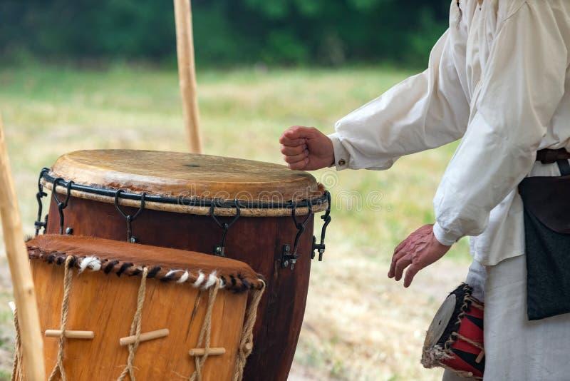 Руки человека играя кожаный outdoors барабанчика пока носящ сельские одежды Традиционное племенное представление барабанчиков стоковые фотографии rf