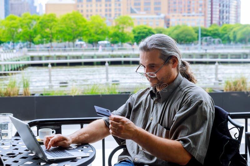 Руки человека используя ноутбук и удержание кредитной карточки с онлайн покупками в свете утра стоковые изображения