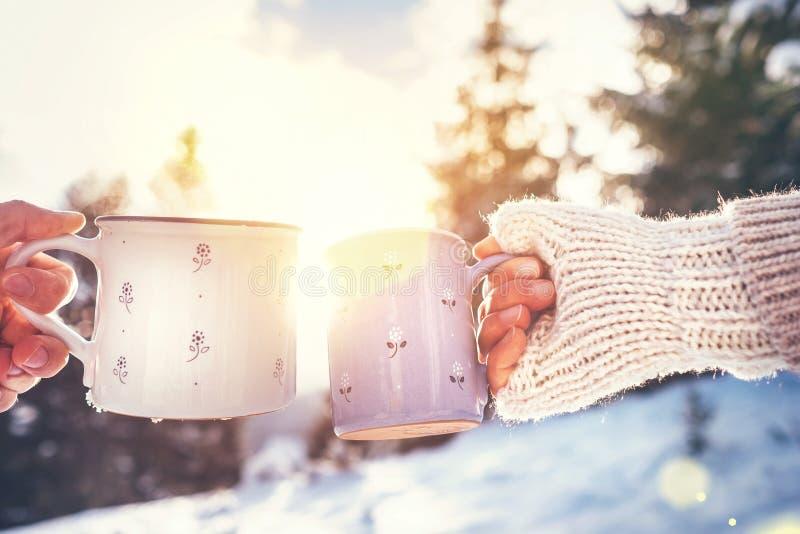 Руки человека и женщины в вязать mittens принимая чашки горячего напитка стоковое изображение rf