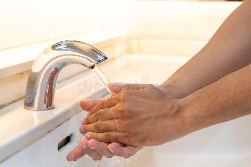 Руки человека крупного плана моя с мылом под faucet стоковая фотография