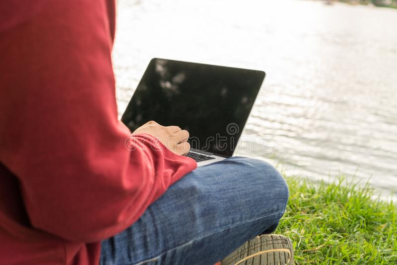 Руки человека печатая на ноутбуке рядом с озером стоковые фото