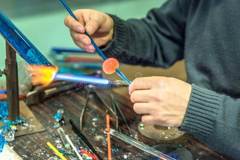 Руки человека ремесленничеств делают стеклянные вопросы стоковая фотография
