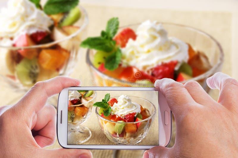 Руки человека со смартфоном принимая фото Диета-свежий вкусный фруктовый салат смешивания в шаре на деревянном столе, здоровые стоковые фото