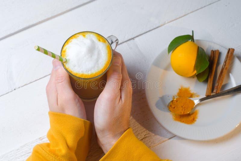 Руки человека с latte турмерина или золотым молоком в стеклах с имбирем и лимонами на белой таблице стоковая фотография