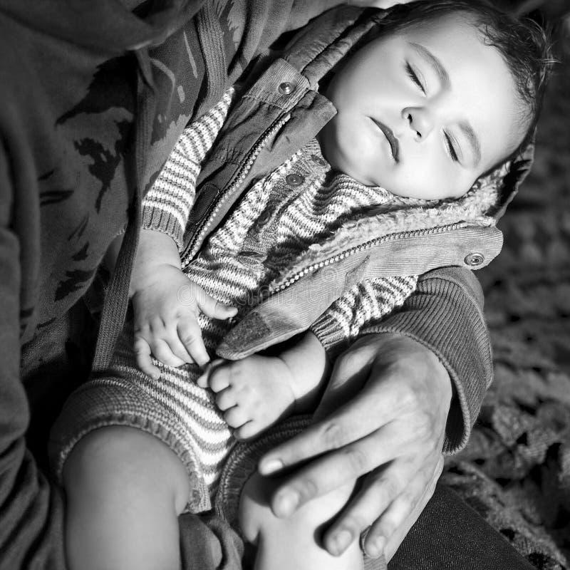 Руки черно-белого изображения мужские держат спать ребенка стоковые фотографии rf