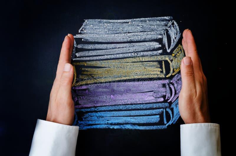 Руки человека держа стог книг нарисованных с мелом стоковое фото rf