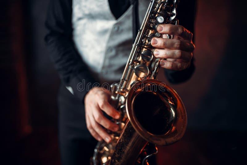 Руки человека джаза держа крупный план саксофона стоковые фотографии rf