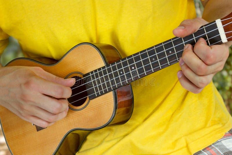 Руки человека играя гавайскую гитару стоковые фото