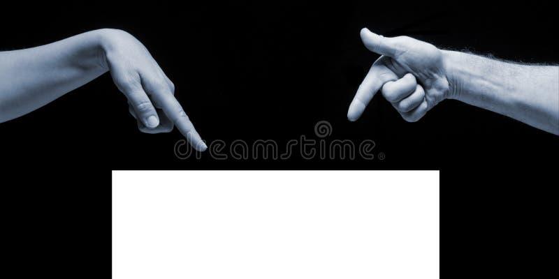 Руки человека и женщины указывая на пустой белый космос экземпляра на черной предпосылке стоковое изображение