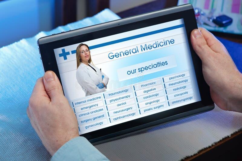 Руки человека смотря вебсайт службы здравоохранения в таблетке стоковая фотография