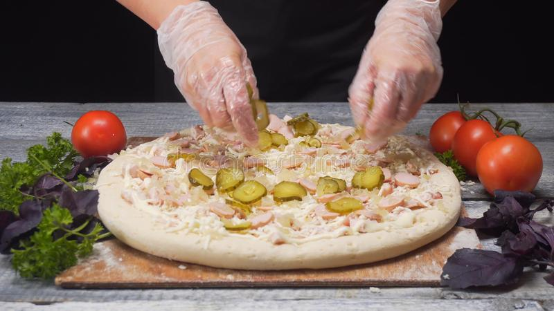 Руки шеф-повара в перчатках силикона принимая часть солениь к его очень вкусной свежей пицце r Итальянская кухня стоковые изображения rf