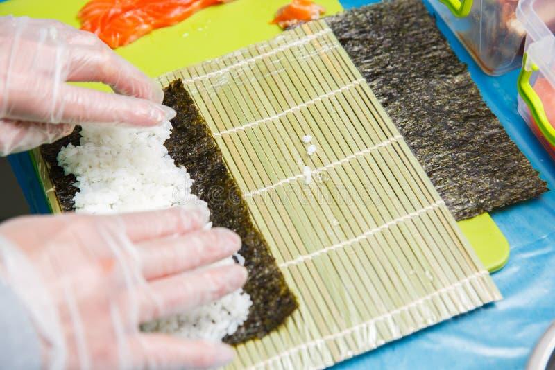 Руки шеф-повара делая на японских кренах суш стоковые изображения