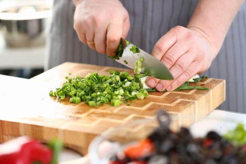 Руки шеф-повара держа лук вырезывания ножа зеленый стоковое изображение rf