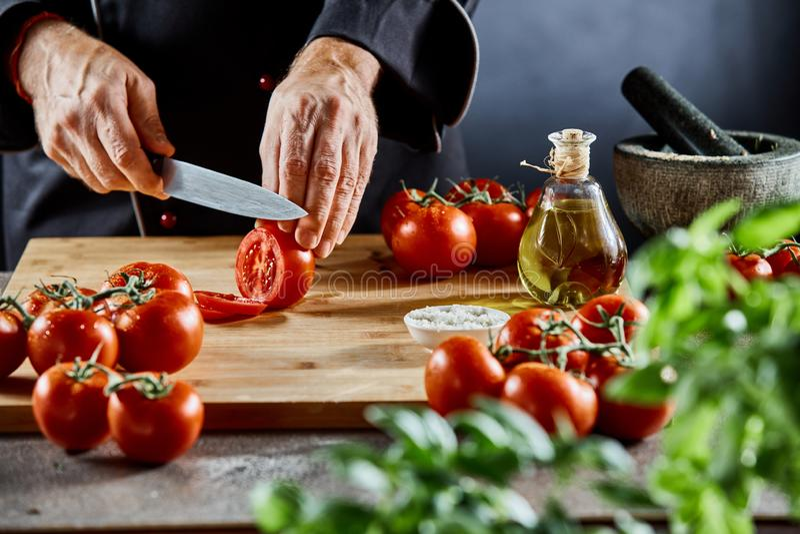 Руки шеф-повара отрезая зрелый томат стоковая фотография rf