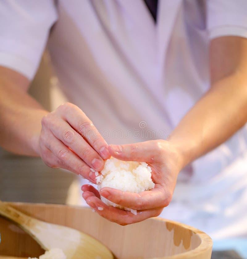 Руки шеф-повара подготавливая японскую кухню, шеф-повара делая суши, подготавливая стоковые изображения