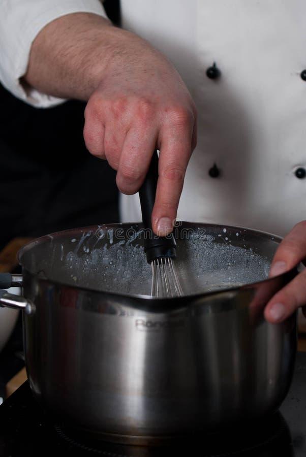 Руки шеф-повара смешивая тесто блинчика в шаре металла Смешивая компоненты Блинчики выпечки в прогрессе Вертикальное изображение стоковые фотографии rf