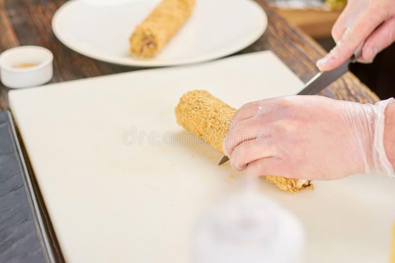 Руки шеф-повара с креном суш вырезывания ножа стоковая фотография
