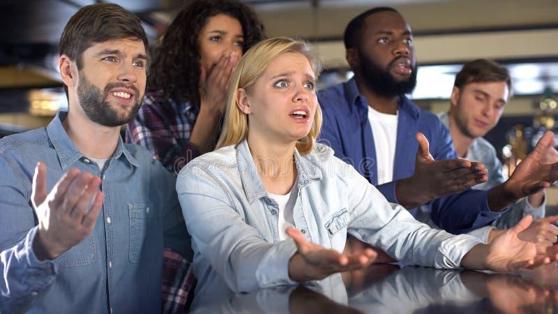 Руки эмоциональных мульти-этнических друзей поднимая, осадили с любимой потерей команды стоковое изображение