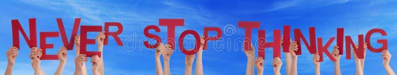 Руки людей держа красное слово никогда не останавливают думать голубое небо стоковое изображение