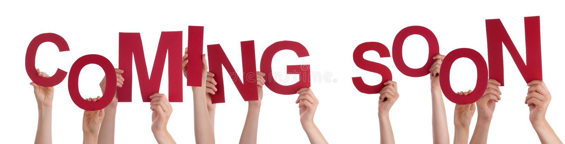 Руки людей держа красное слово приходя скоро стоковые фотографии rf