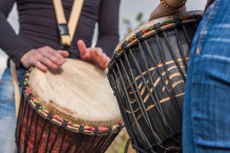 Руки людей играя музыку на барабанчиках djembe стоковое изображение