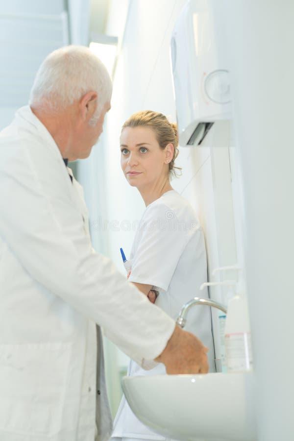Руки Dcotor моя и говорить к медсестре стоковые изображения