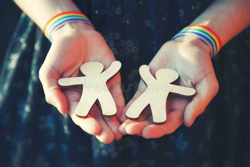 Руки Emale с wristbands ленты радуги LGBT держа пар мини деревянных людей стоковые фото