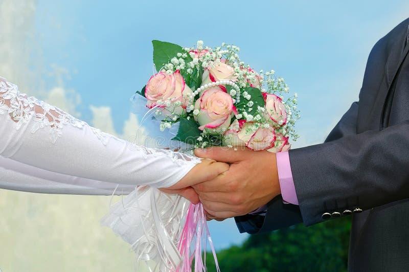 Руки groom и невесты с букетом свадьбы стоковое фото