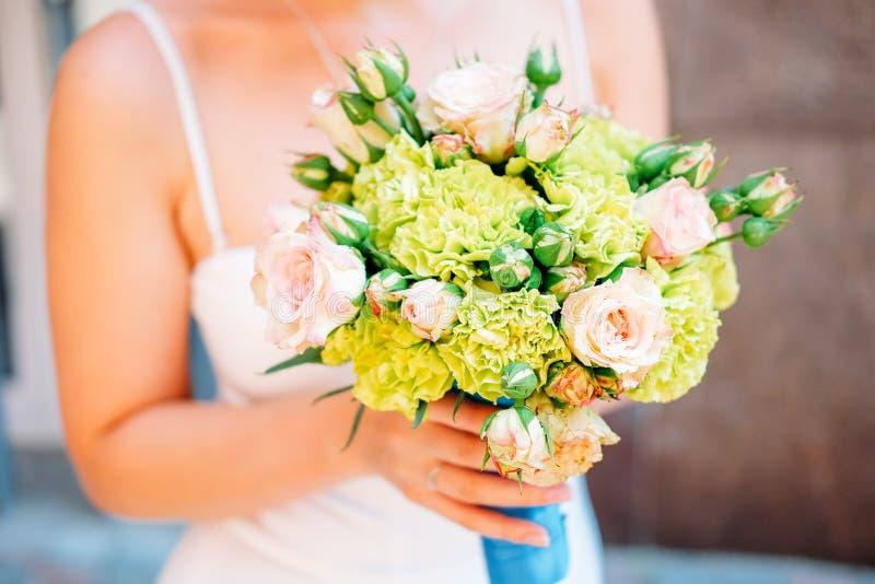 руки groom невесты букета bridal Свежие желтые и зеленые цветки с голубой лентой стоковое изображение rf