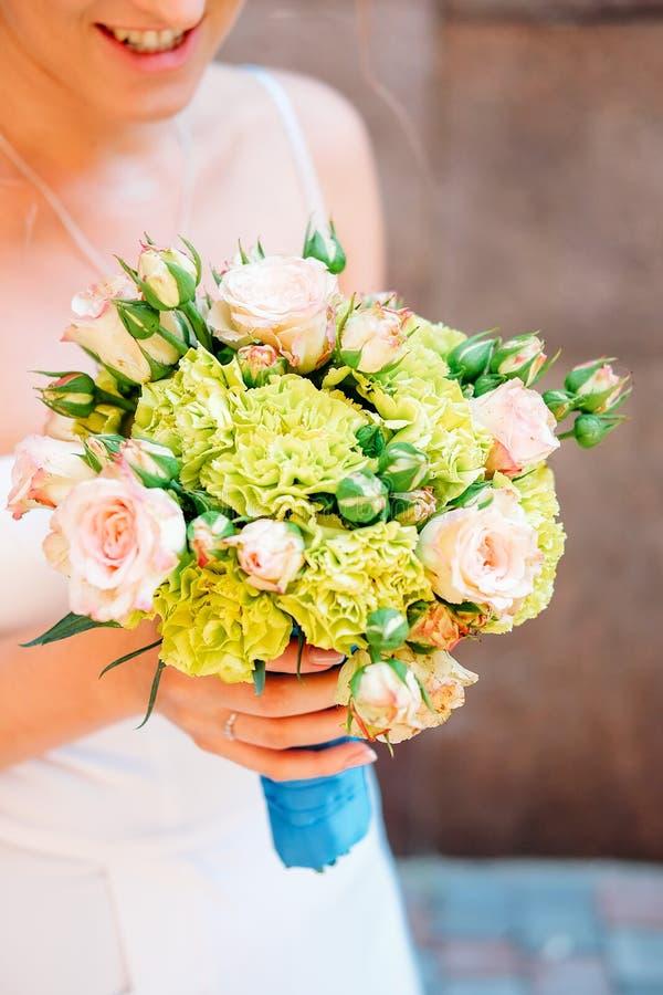 руки groom невесты букета bridal Свежие желтые и зеленые цветки с голубой лентой стоковое фото