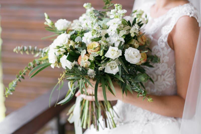 руки groom невесты букета bridal ` S невесты Красивый белых цветков и растительности, украшенный с silk лентой, лежит на годе сбо стоковая фотография rf
