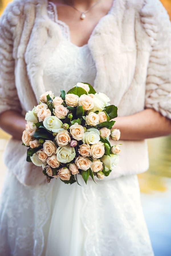 руки groom невесты букета bridal ` S невесты Красивый белых цветков и растительности, украшенный с silk лентой, лежит на годе сбо стоковое фото