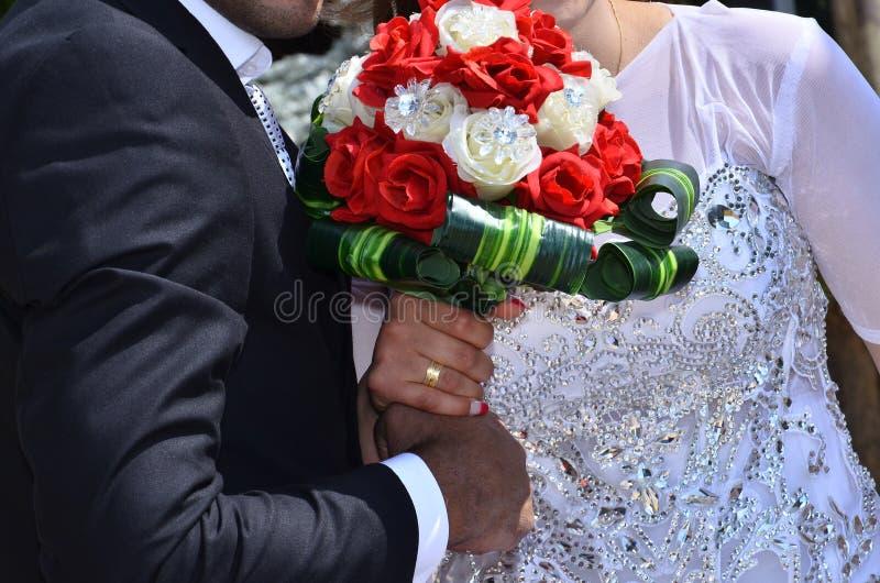 Руки ` s жениха и невеста держат bridal букет цветков шарлаха стоковые изображения rf