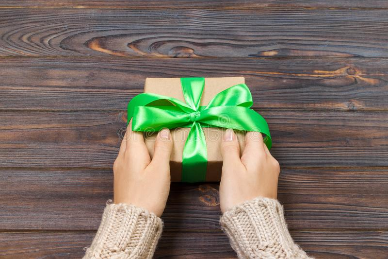 Руки ` s женщины дают обернутый настоящий момент праздника валентинки handmade в бумаге ремесла с зеленой лентой Присутствующая к стоковые изображения