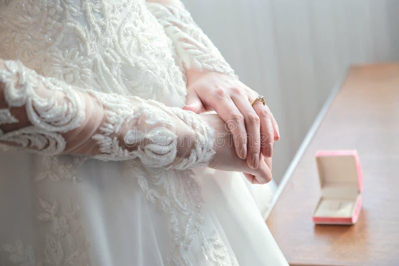 Руки ` s женщин на белом платье свадьбы покажите ее обручальное кольцо с коробкой в предпосылке стоковые изображения