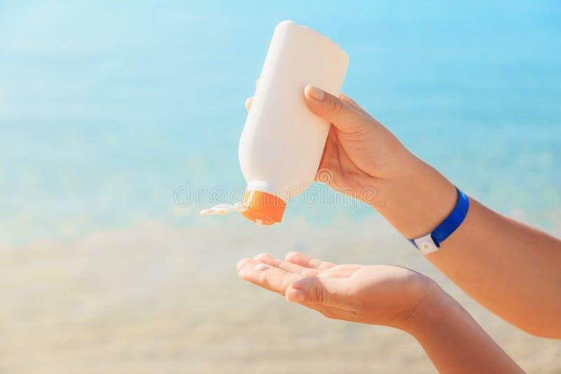 Руки ` s женщин прикладывают лосьон suntan к коже стоковая фотография rf