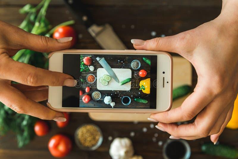 Руки ` s женщин с телефоном фотографируют овощи стоковая фотография rf