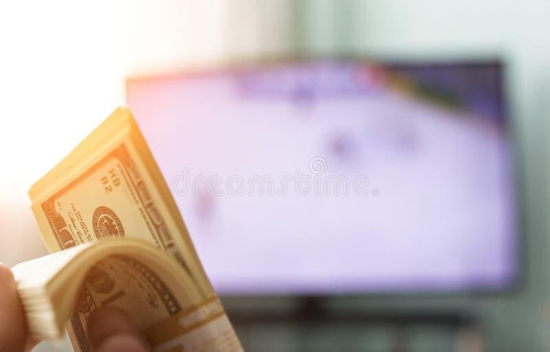 Руки ` s людей держат пачку долларов денег на фоне ТВ на котором они показывают хоккей, конц-поднимают стоковое фото
