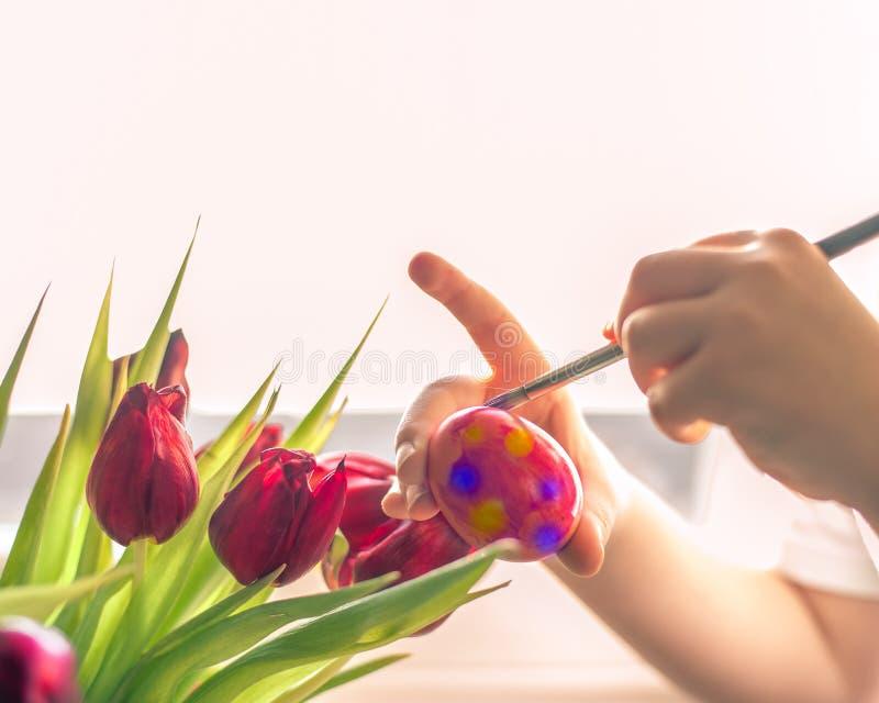 Руки ` s ребенка украшая пасхальное яйцо Отрицательный космос стоковые фотографии rf