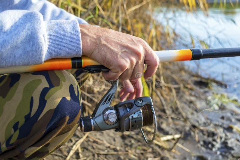 Руки ` s рыболова держат закручивая штангу стоковое фото rf
