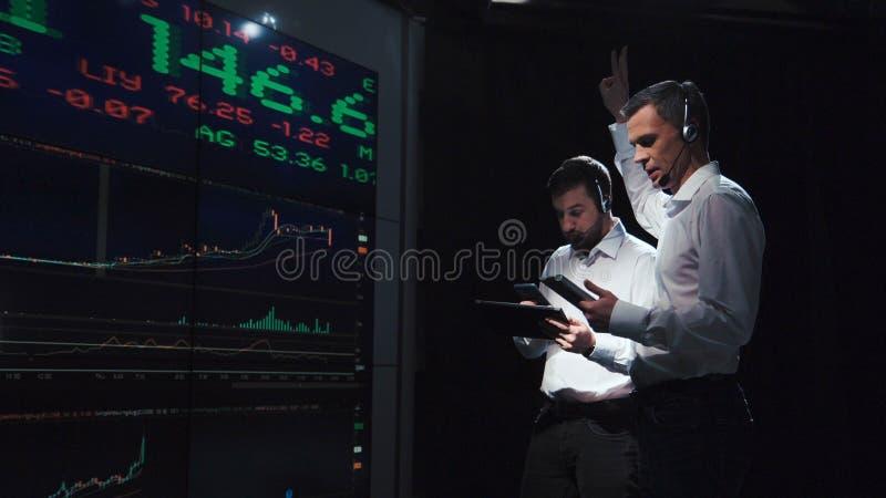 Руководители группы биржевого маклера перед прямой трансляцией стоковое изображение rf
