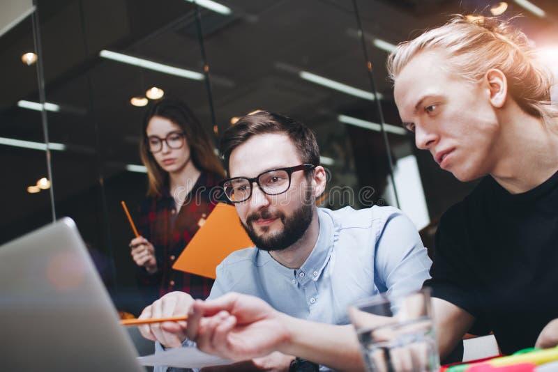 Руководитель проекта исследуя процесс Команда Coworking работая совместно на новом sturt вверх Молодые люди и использование прият стоковые фото