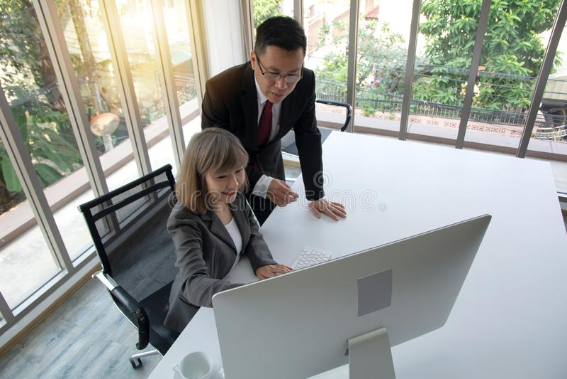 Руководитель фирмы тренируя молодых ассистента, руководителя группы или высшего руководителя личного секретаря объясняя обязаннос стоковое фото rf