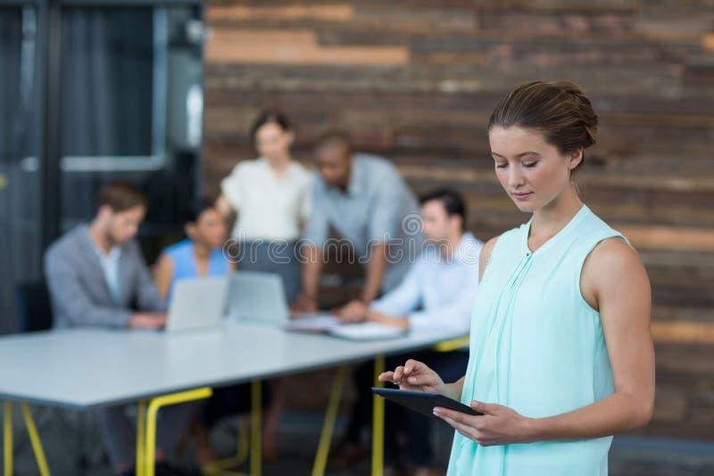 Руководитель бизнеса используя цифровую таблетку в офисе стоковое изображение rf