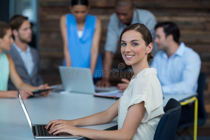 Руководитель бизнеса сидя на таблице и используя компьтер-книжку в офисе стоковые изображения