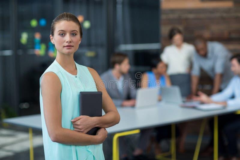 Руководитель бизнеса стоя с цифровой таблеткой в офисе стоковые изображения rf