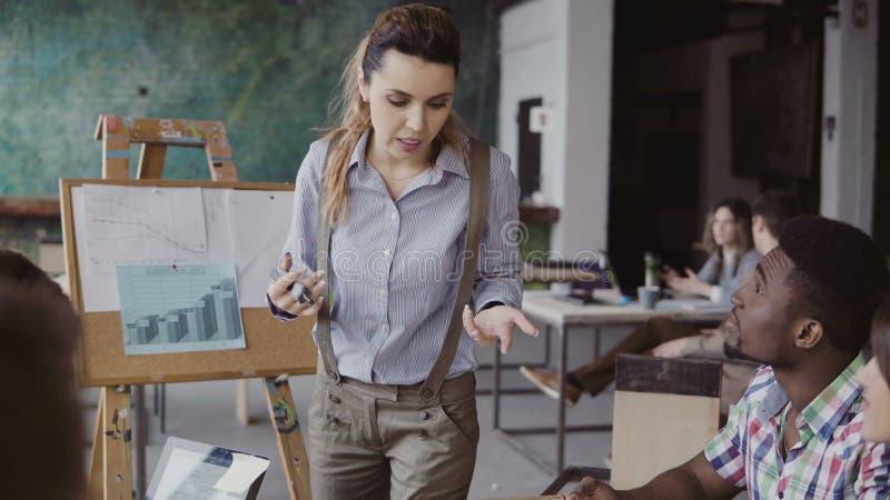 Руководитель группы брюнет женский разговаривая с смешанной группой лицо одной расы людей, пишет с отметкой на модели дома стоковые изображения